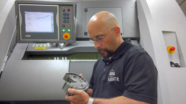 Jarod Rauch holds a 3d printed conformally cooling part in front of the DMP 300