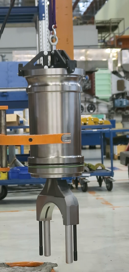 a large engine workpiece being lifted by a 3d printed crane claw, made of chopped carbon fiber called Onyx